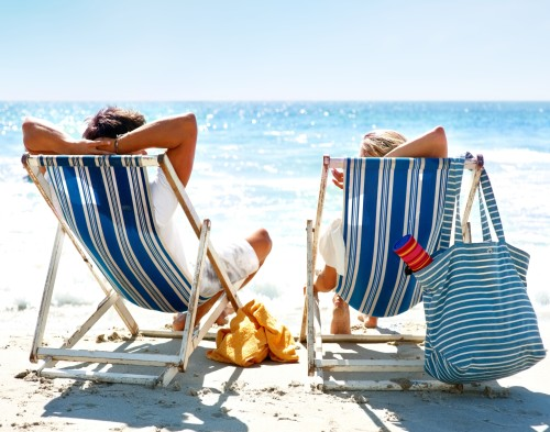 View of a couple sitting on deck chairs enjoying vacation